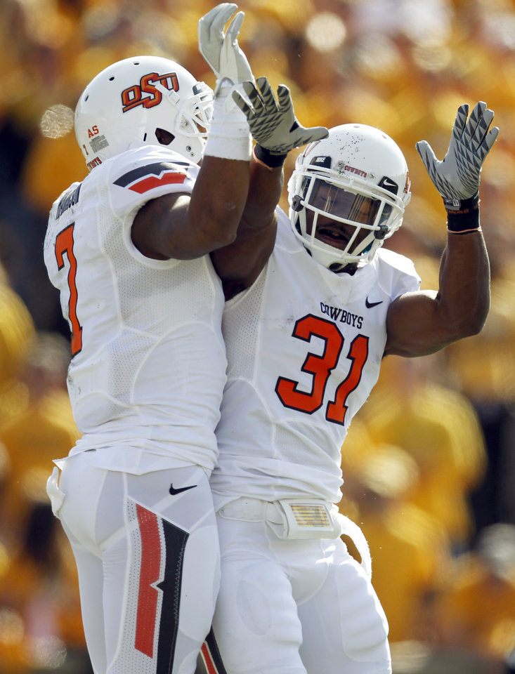 Photo - Oklahoma State wide receiver Michael Harrison, left, is congratulated by  teammate Jeremy Smith after Harrison caught a 27-yard touchdown pass during the first half of an NCAA college football game against Missouri Saturday, Oct. 22, 2011, in Columbia, Mo. (AP Photo/Jeff Roberson)