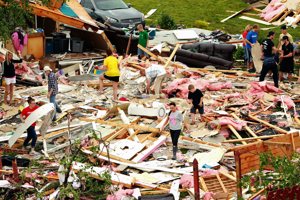 People search and gather items after a storm destroyed a house on Haversham Drive Saturday, June 1, 2013 in St. Charles County, Mo. The National Weather Service confirms at least two tornados were part of the Friday night storm that raked portions of the St. Louis area, damaging hundreds of homes but causing no serious injuries. (AP Photo/St. Louis Post-Dispatch, Huy Mach)  EDWARDSVILLE INTELLIGENCER OUT; THE ALTON TELEGRAPH OUT