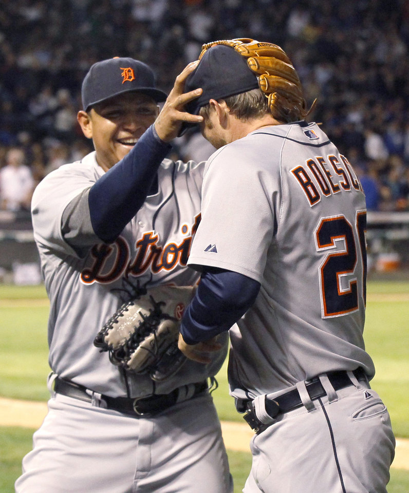 Photo -   Detroit Tigers' Miguel Cabrera, left, greets Brennan Boesch at the dugout after Boesch made a diving catch on a fly ball hit by Chicago Cubs' David DeJesus to end the seventh inning of an interleague baseball game Wednesday, June 13, 2012, in Chicago. (AP Photo/Charles Rex Arbogast)