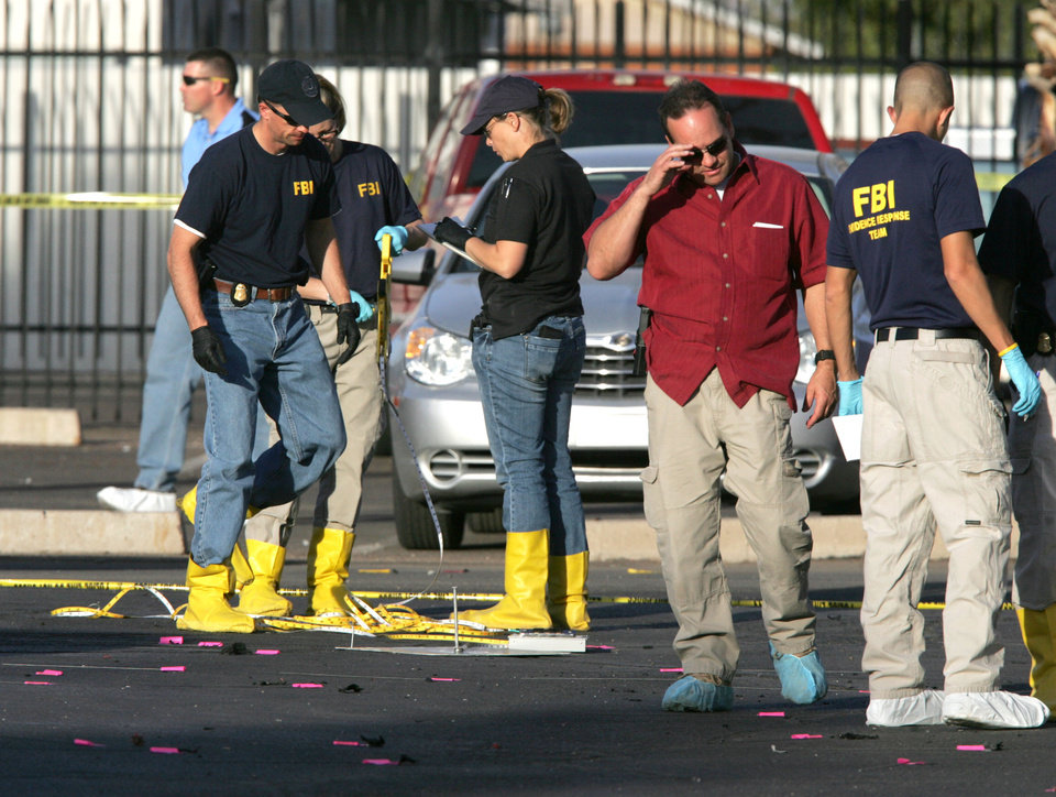 Photo - Federal agents investigate an apparent bomb explosion at the Social Security Administration office on Marshall Street in downtown Casa Grande, Ariz. on Friday, Nov. 30, 2012. No one was hurt in the explosion. (AP Photo/Casa Grande Dispatch, Oscar Perez)