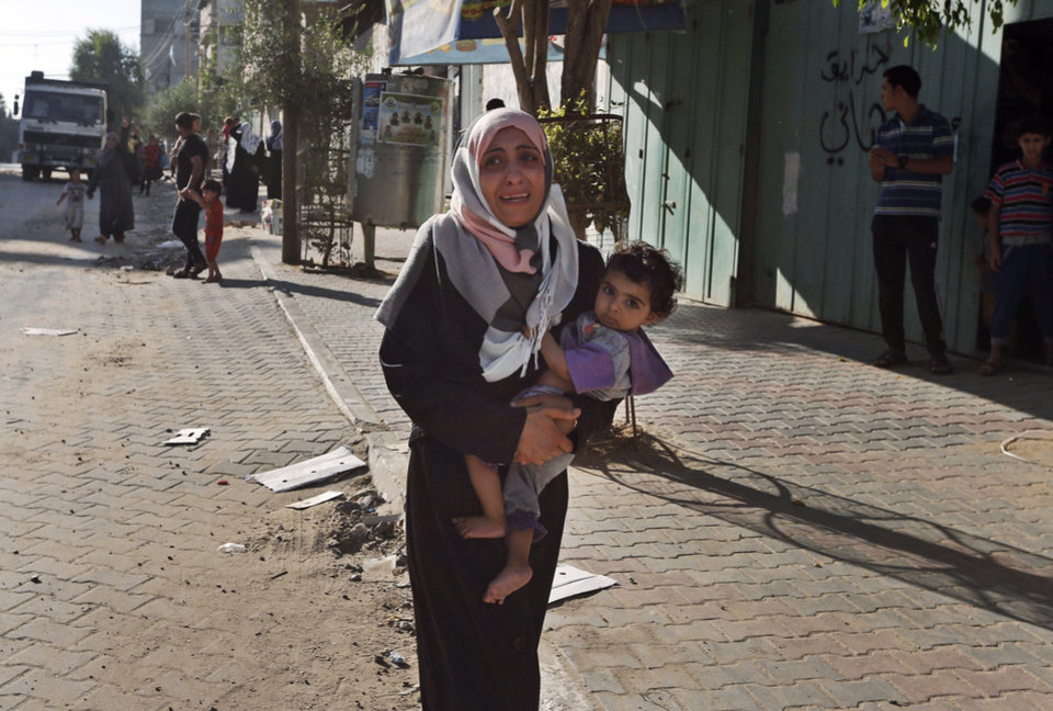 Photo - A woman cries as Palestinians flee their homes in the Shajaiyeh neighborhood of Gaza City, after Israel had airdropped leaflets warning people to leave the area, Wednesday, July 16, 2014. A Hamas website says Israel has fired missiles at the homes of four of its senior leaders as it resumed bombardment of Gaza, following a failed Egyptian cease-fire effort. Health officials say the Palestinian death toll in nine days of fighting has reached 204.(AP Photo/Lefteris Pitarakis)