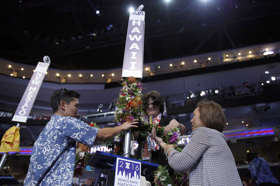 Photo - Jaren McCartney, Heather Murakami and Flo Kong Kee decorate Hawaii state sign before the start of the first day of the Democratic National Convention in Philadelphia, Monday, July 25, 2016. (AP Photo/Matt Rourke)