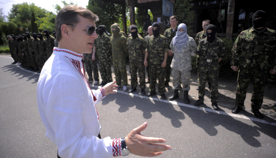 Photo - Oleh Lyashko, left, leader of Ukrainian Radical Party and presidential candidate, speaks to  self defense volunteers at a training ground outside Kiev, Ukraine, Friday, May 23, 2014. Ukraine is holding a presidential election Sunday but it has become downright dangerous for many in the east to be associated with the vote, since the eastern regions of Donetsk and Luhansk declared independence last week. Ukrainian police and election officials accuse pro-Russia gunmen there of seizing election commission offices and threatening members in an effort to derail the presidential vote. (AP Photo/Osman Karimov)