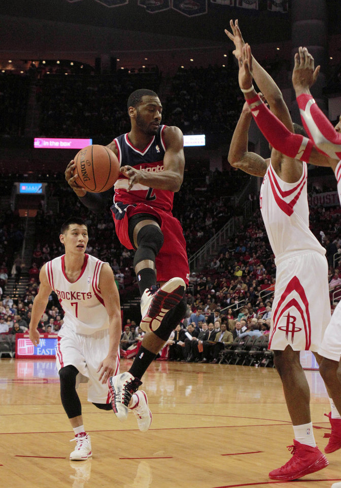 Photo - Washington Wizards guard John Wall (2) goes up to shoot followed by Houston Rockets guard Jeremy Lin (7) during the first half of an NBA basketball game in Houston, Wednesday, Feb. 12, 2014. (AP Photo/Richard Carson)