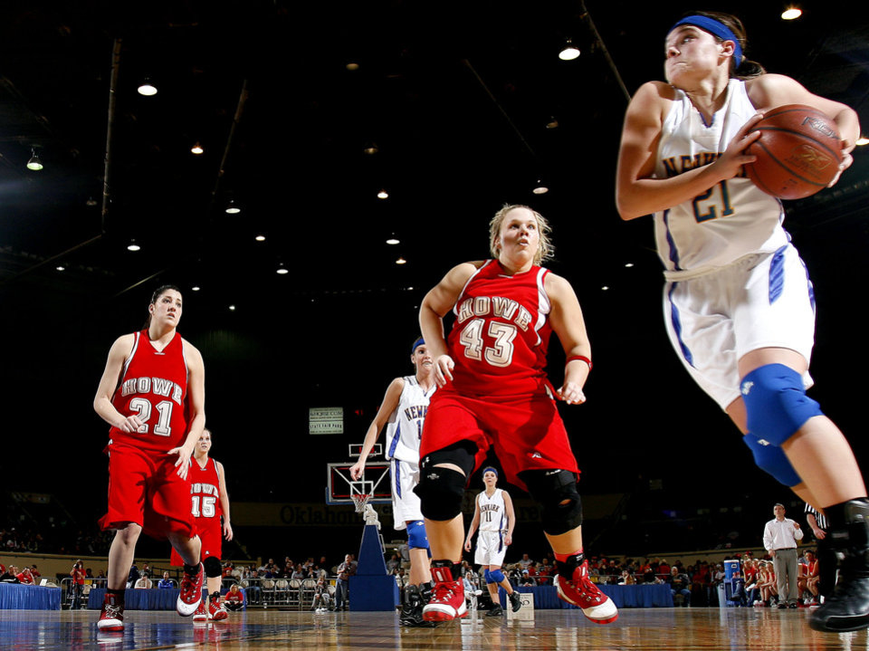 Photo - Newkirk's Megan Schieber (21) drives to the basket as Howe's Samantha Carter (43) and Katie BenAmor (21) defend during the girls 2A semifinal between Howe and Newkirk at the State Fair Arena, Friday, March 13, 2009, in Oklahoma City. PHOTO BY SARAH PHIPPS, THE OKLAHOMAN