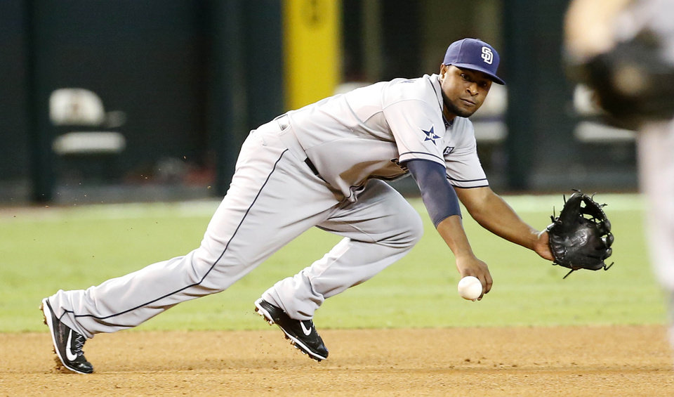 Photo - San Diego Padres' third baseman Chris Nelson dives for a grounder in the fourth inning against the Arizona Diamondbacks during a baseball game, Sunday, Aug. 24, 2014, in Phoenix.  Nelson fielded the ball and threw to second for a force out. (AP Photo/Darryl Webb)