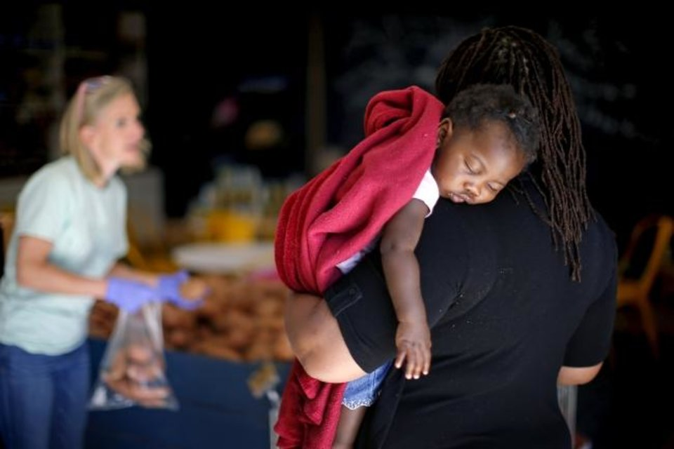 Photo -  Shaquice Muyanga holds her daughter Nadia, 1, as she shops inside on Thursday at The Market at Restore OKC in Oklahoma City. [Bryan Terry/The Oklahoman]