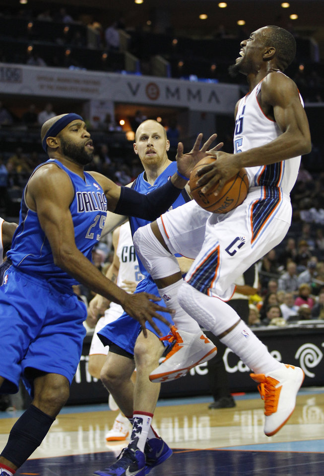 Charlotte Bobcats' Kemba Walker, right, is fouled as he drives on Dallas Mavericks' Vince Carter, left, and Chris Kaman, back, during the first half of an NBA basketball game in Charlotte, N.C., Saturday, Nov. 10, 2012. (AP Photo/Chuck Burton)