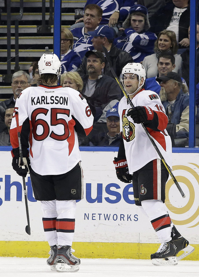 Photo - Ottawa Senators left wing Clarke MacArthur (16) celebrates his goal against the Tampa Bay Lightning with teammate Erik Karlsson (65) during the second period of an NHL hockey game Thursday, Jan. 23, 2014, in Tampa, Fla. (AP Photo/Chris O'Meara)