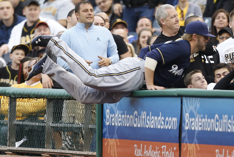 Photo - Milwaukee Brewers third baseman Mark Reynolds dives into the stands after a foul ball in the first inning of a baseball game against the Pittsburgh Pirates on Saturday, April 19, 2014, in Pittsburgh. (AP Photo/Keith Srakocic)