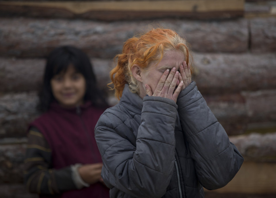 Photo - Minka Ruseva, daughter of Sasha Ruseva,  covers her face in a Roma neighborhood of Nikolaevo, Bulgaria, Friday, Oct. 25, 2013. Sasha Ruseva, a Bulgarian Roma woman, is  under investigation by Bulgarian authorities trying to find out  if she is the mother of a suspected abduction victim in neighboring Greece known as