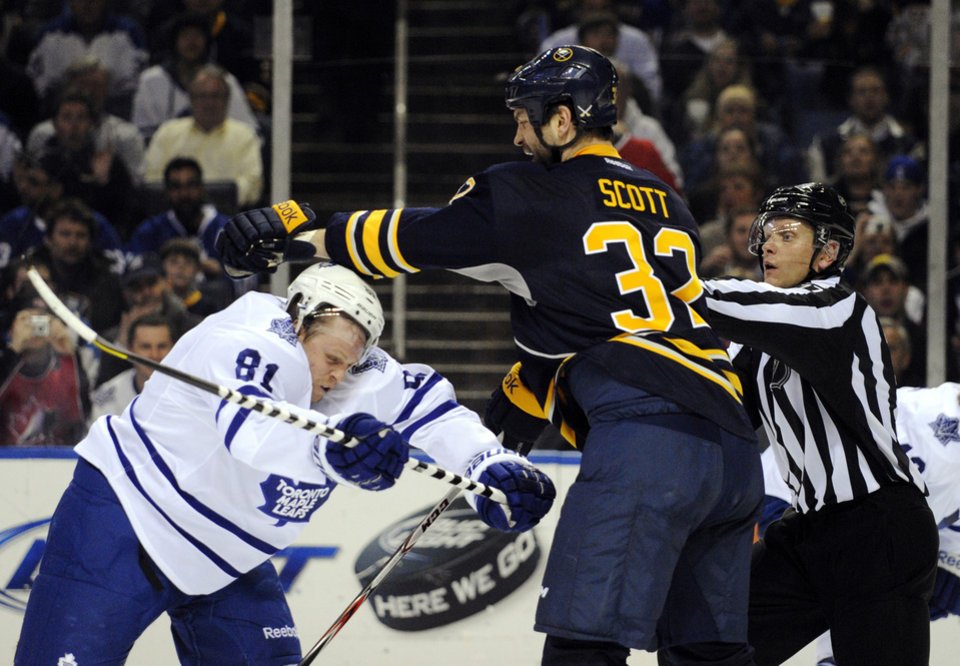 Toronto Maple Leafs right winger Phil Kessel (81) gets cross-checked by Buffalo Sabres left winger John Scott (32) during the second period of an NHL hockey game in Buffalo, N.Y., Thursday, March 21, 2013. (AP Photo/Gary Wiepert)