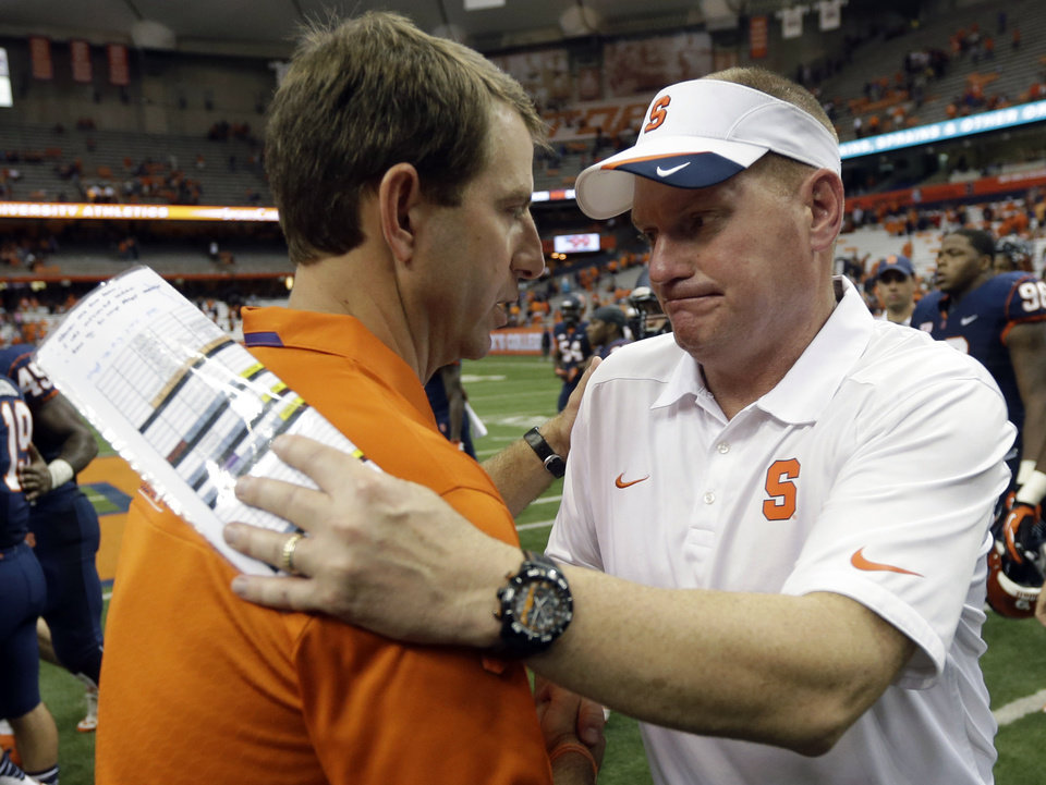 Photo - Clemson head coach Dabo Swinney, left, and Syracuse head coach Scott Shafer shakes hands after an NCAA college football game on Saturday, Oct. 5, 2013, in Syracuse, N.Y. Clemson won, 49-14. (AP Photo/Mike Groll)