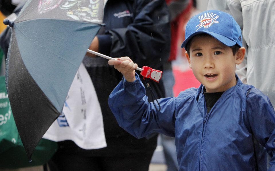 Photo - Fan Michael Cole, 7, cheers with his umbrella during the Thunder FanFest in Bricktown, celebrating the team making it to the NBA playoffs, in Oklahoma City, Friday, April 16, 2010. Photo by Nate Billings, The Oklahoman