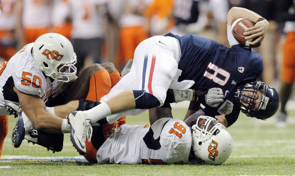 Photo - OSU's Ugo Chinasa (91) sacks Arizona quarterback Nick Foles (8) with the help of OSU's Jamie Blatnick (50) in the first quarter during the Valero Alamo Bowl college football game between the Oklahoma State University Cowboys (OSU) and the University of Arizona Wildcats at the Alamodome in San Antonio, Texas, Wednesday, December 29, 2010. Photo by Nate Billings, The Oklahoman