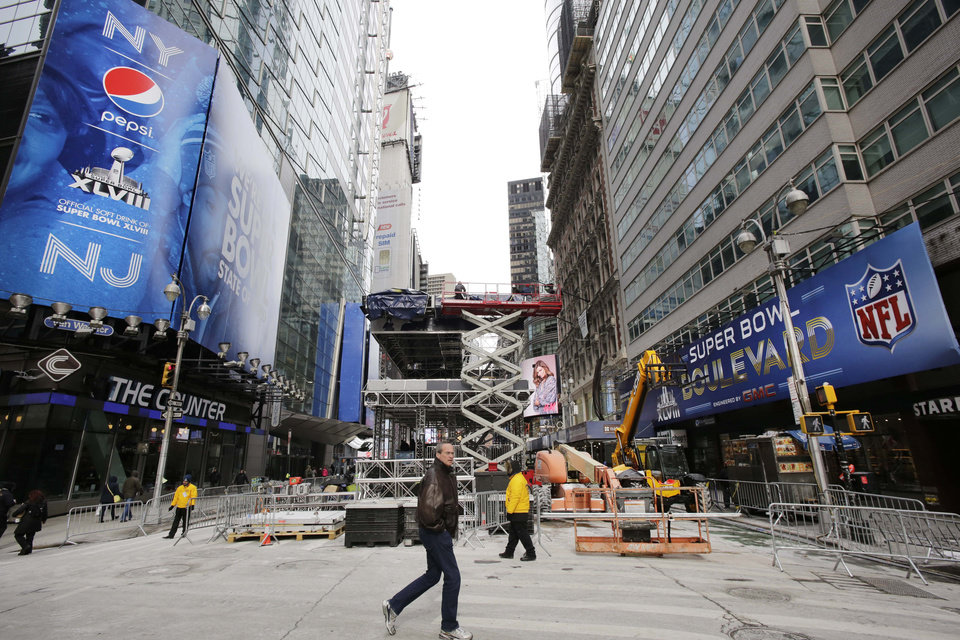 Photo - A pedestrian passes a soundstage under construction in New York's Times Square, Sunday, Jan. 26, 2014. A dozen blocks of Broadway, in the heart of Manhattan, will close to traffic for four days so the NFL can host a Super Bowl festival. The championship football game between the Denver Broncos and Seattle Seahawks is Sunday, Feb. 3 in East Rutherford, N.J. (AP Photo/Mark Lennihan)