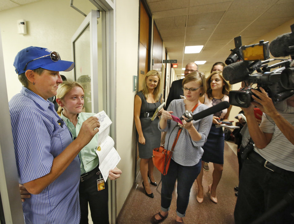 Photo - Jennifer Hasler, left, and Karina Tittjung show their marriage license to members of the media at the Oklahoma County Courthouse in Oklahoma City, Monday October, 6 2014.They were the 2nd same sex couple to receive a marriage license in Oklahoma County. Photo By Steve Gooch, The Oklahoman