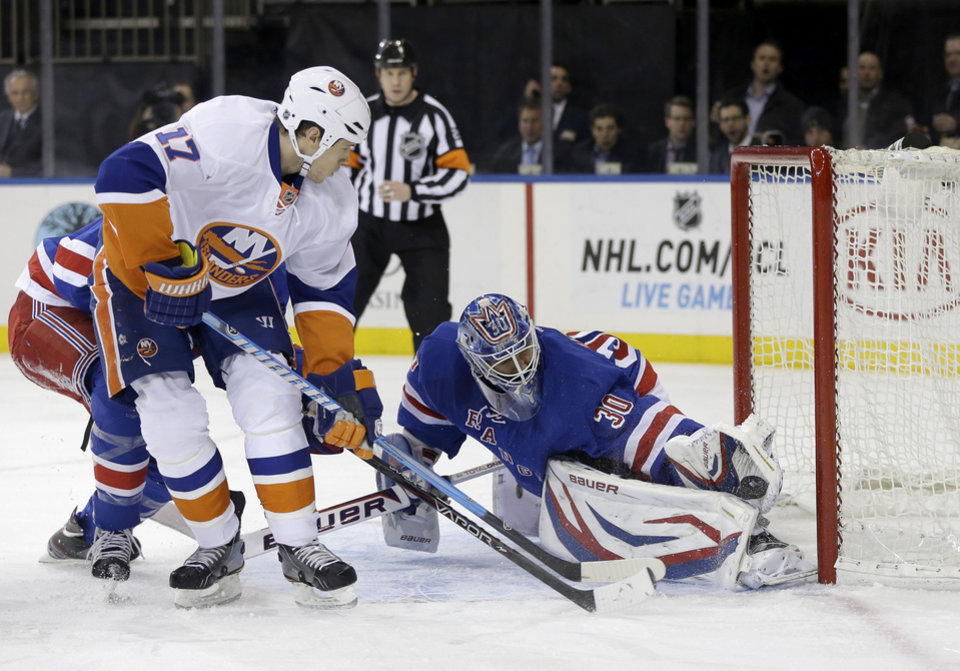 New York Rangers goalie Henrik Lundqvist, right, blocks a shot by New York Islanders' Matt Martin (17) during the first period of the NHL hockey game in New York, Thursday, Feb. 7, 2013. (AP Photo/Seth Wenig)