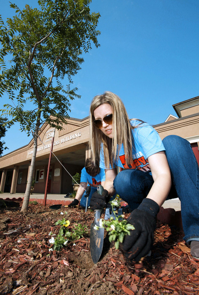 United Way volunteer Shelley Pirkle, of First American Bank, plants flowers Friday in front of the Community Services Building in Norman.