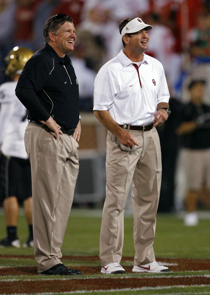 Photo - Colorado head coach Dan Hawkins and Oklahoma head coach Bob Stoops talk before the college football game between the University of Oklahoma (OU) Sooners and the University of Colorado Buffaloes at Gaylord Family-Oklahoma Memorial Stadium in Norman, Okla., Saturday, October 30, 2010.  Photo by Steve Sisney, The Oklahoman