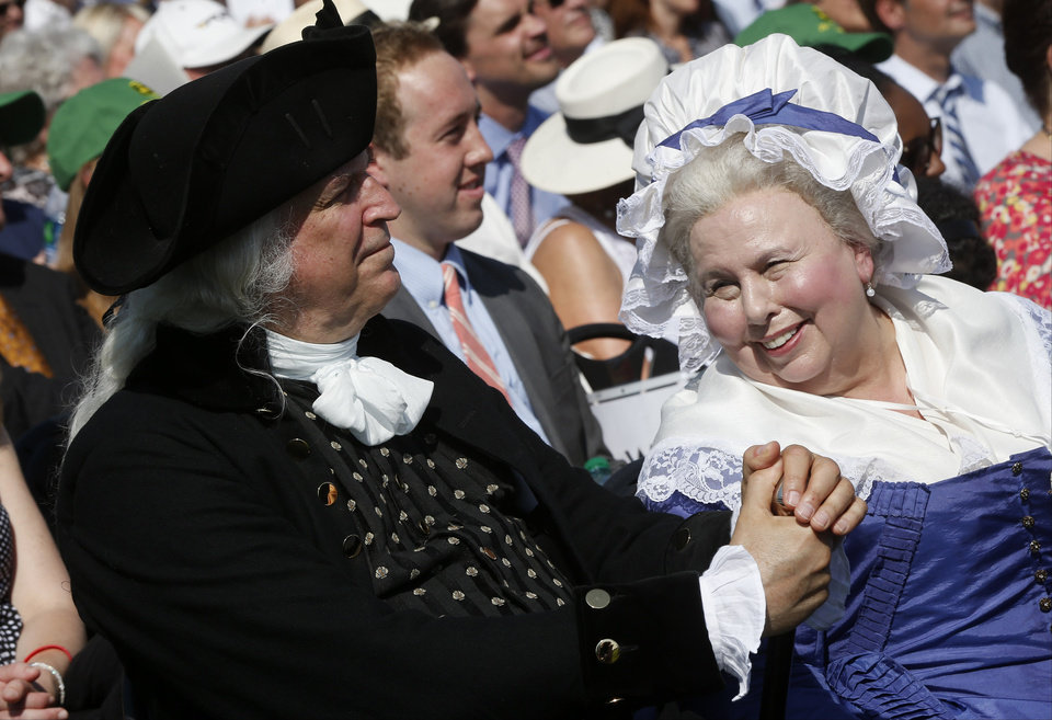Photo - George Washington played by Dean Malissa, left, and Martha Washington played by Mary Wiseman, attend a ceremony to celebrate the re-opening of the Washington Monument, Monday, May 12, 2014, in Washington. The monument, which sustained damage from an earthquake in August 2011, reopened to the public today. (AP Photo)