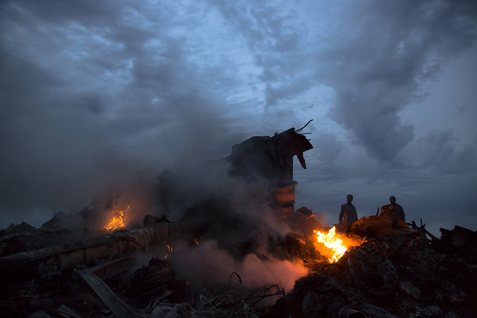 Photo - People walk amongst the debris at the crash site of a passenger plane near the village of Hrabove, Ukraine, Thursday, July 17, 2014. Ukraine said a passenger plane was shot down Thursday as it flew over the countr. Both the government and the pro-Russia separatists fighting in the region denied any responsibility for downing the plane. (AP Photo/Dmitry Lovetsky)
