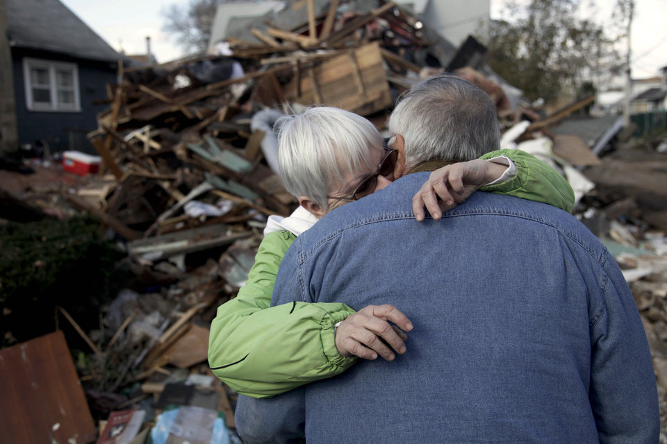 Sheila and Dominic Traina hug in front of their home which was demolished during Superstorm Sandy in Staten Island, N.Y., Friday, Nov. 2, 2012.  Mayor Michael Bloomberg has come under fire for pressing ahead with the New York City Marathon. Some New Yorkers say holding the 26.2-mile race would be insensitive and divert police and other important resources when many are still suffering from Superstorm Sandy. The course runs from the Verrazano-Narrows Bridge on hard-hit Staten Island to Central Park, sending runners through all five boroughs. The course will not be changed, since there was little damage along the route.  (AP Photo/Seth Wenig) ORG XMIT: NYSW106