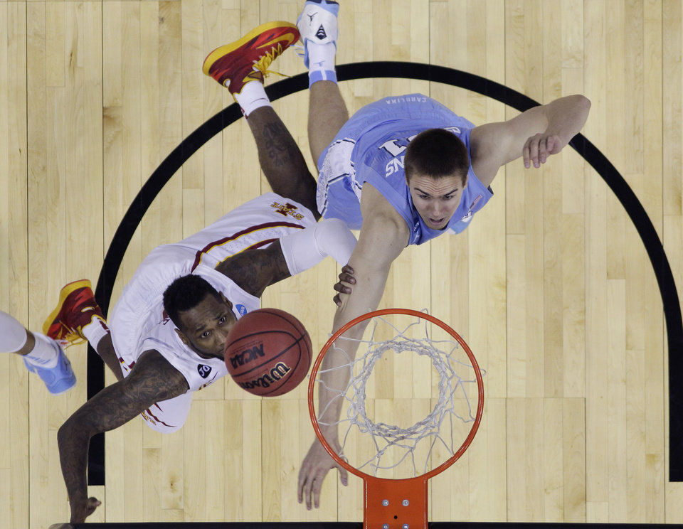 Photo - Iowa State's DeAndre Kane, left, makes the winning shot over North Carolina's Jackson Simmons, right, in the final seconds of the second half of a third-round game in the NCAA college basketball tournament Sunday, March 23, 2014, in San Antonio. Iowa State won 85-83. (AP Photo/Eric Gay)