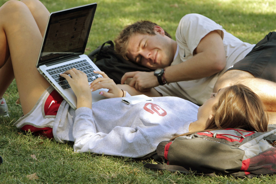 Photo - OU: Freshmen Emma Morris, Oklahoma City, and Jacob Hanlon, Midwest City, lay out on the south oval as students enjoy the warm weather on the campus of the University of Oklahoma on Tuesday, September 27, 2011, in Norman, Okla.   Photo by Steve Sisney, The Oklahoman ORG XMIT: KOD