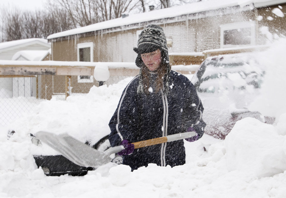 Photo - Elizabeth Else, 15, shovels out her family's driveway Monday, Feb. 11, 2013, in Fargo, N.D. Schools, public offices, medical centers and businesses throughout the eastern Dakotas opened late or not at all Monday as the region began digging out from a blizzard that broke several longstanding weather records. (AP Photo/The Forum, Michael Vosburg)