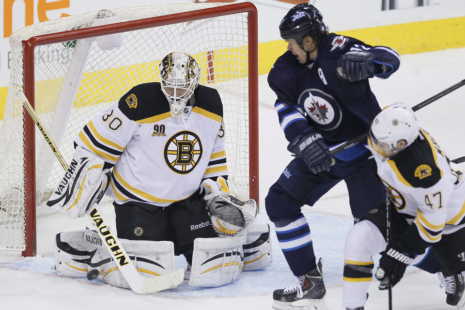 Photo - Boston Bruins goaltender Chad Johnson (30) saves a shot as Winnipeg Jets' Olli Jokinen (12) and Bruins' Torey Krug (47) look for a rebound during the first period of an NHL hockey game Thursday, April 10, 2014, in Winnipeg, Manitoba. (AP Photo/The Canadian Press, John Woods)
