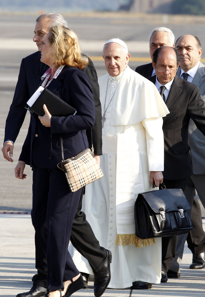 Photo - Pope Francis holds a bag at Rome's Fiumicino international airport, Monday, July 22, 2013. It's wheels up on Pope Francis' first trip abroad as pontiff. A special Alitalia flight carrying Francis, his entourage and journalists who will cover him on his week-long visit to Brazil took off 10 minutes behind schedule Monday from Rome's Leonardo da Vinci airport. Keeping to his example that the Catholic church must be humble, Francis carried his own black hand luggage. He even kept holding it with his left hand while he used his left to shake hands with some of the VIPs who turned out to wish him well and while he climbed the stairs to the jet's entrance. Among the dignitaries was Italian Premier Enrico Letta. (AP Photo/Riccardo De Luca)