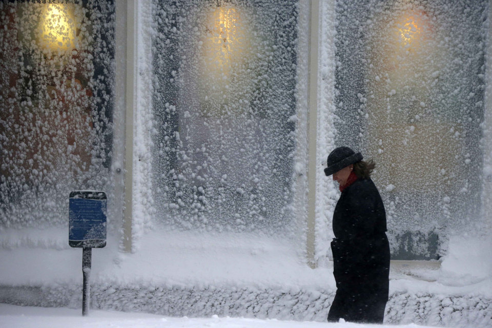 Photo - A woman walks past windows covered with snow at the Seaport World Trade Center in Boston early Saturday, Feb. 9, 2013. (AP Photo/Gene J. Puskar)
