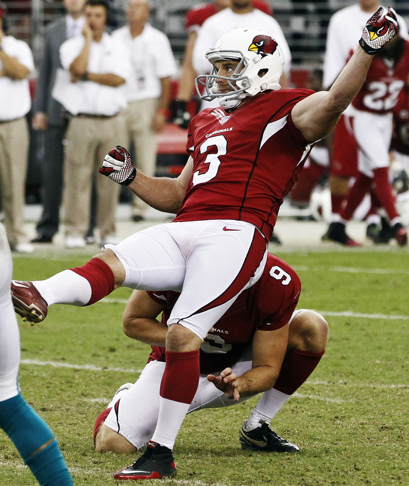 Arizona Cardinals' Jay Feely (3) watches his winning kick against the Miami Dolphins as holder Dave Zastudil (9) kneels during overtime of an NFL football game, Sunday, Sept. 30, 2012, in Glendale, Ariz. The Cardinals won 24-21. (AP Photo/Ross D. Franklin)