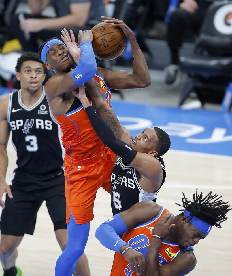 Photo - Oklahoma City's Shai Gilgeous-Alexander (2) fights for the ball with San Antonio's Dejounte Murray (5) during an NBA basketball game between the Oklahoma City Thunder and the San Antonio Spurs at Chesapeake Energy Arena in Oklahoma City, Tuesday, Jan. 12, 2021.  San Antonio won 112-102. [Bryan Terry/The Oklahoman]