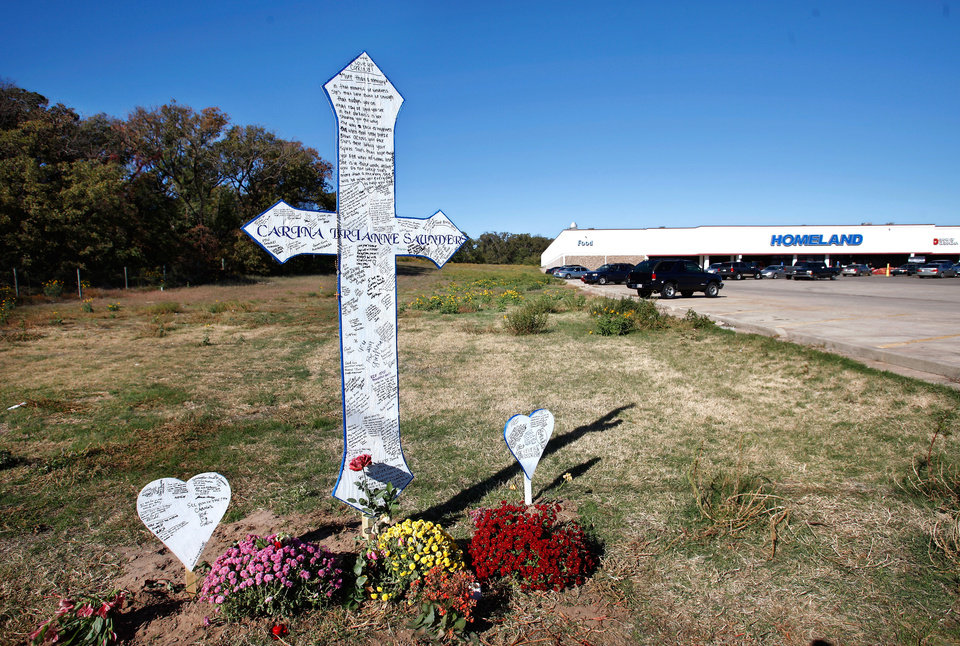 Family and friends recently placed a large white cross as a memorial to Carina Saunders, 19, in a field on the north side of NW 23 Street west of Rockwell Avenue in Bethany. Saunders\' dismembered body was found in a duffel bag in a field next to a national chain grocery store on Oct. 13. Police continue to search for her killer. This photo taken Thursday, Nov. 3, 2011. Photo by Jim Beckel, The Oklahoman ORG XMIT: KOD