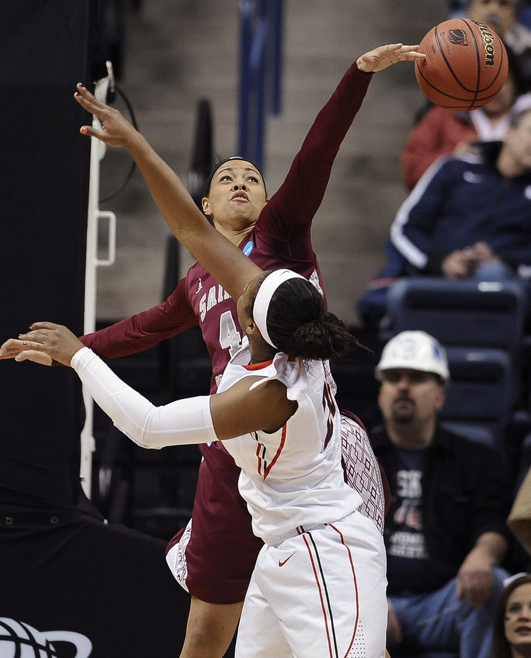 Photo - Saint Joseph's Natasha Cloud, left, blocks the shot of Georgia's Shacobia Barbee, right, during the first half of a first-round game of the NCAA women's college basketball tournament, Sunday, March 23, 2014, in Storrs, Conn. (AP Photo/Jessica Hill)