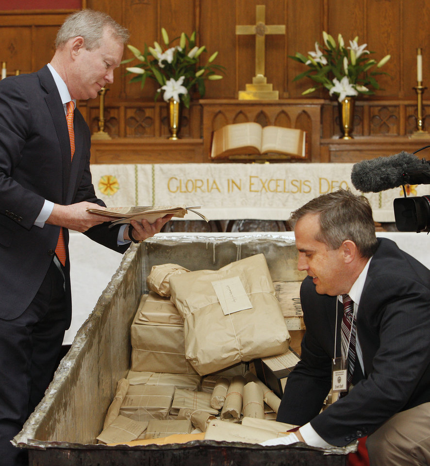 Mayor Mick Cornett looks at a Sunday, April 20, 1913, newspaper as Chad Williams, Oklahoma History Center research division director, removes items from the Century Chest at First Lutheran Church in Oklahoma City Monday, April 22, 2013. The Century Chest is a time capsule put together and buried April 22, 1913 by the church. Photo by Paul B. Southerland, The Oklahoman