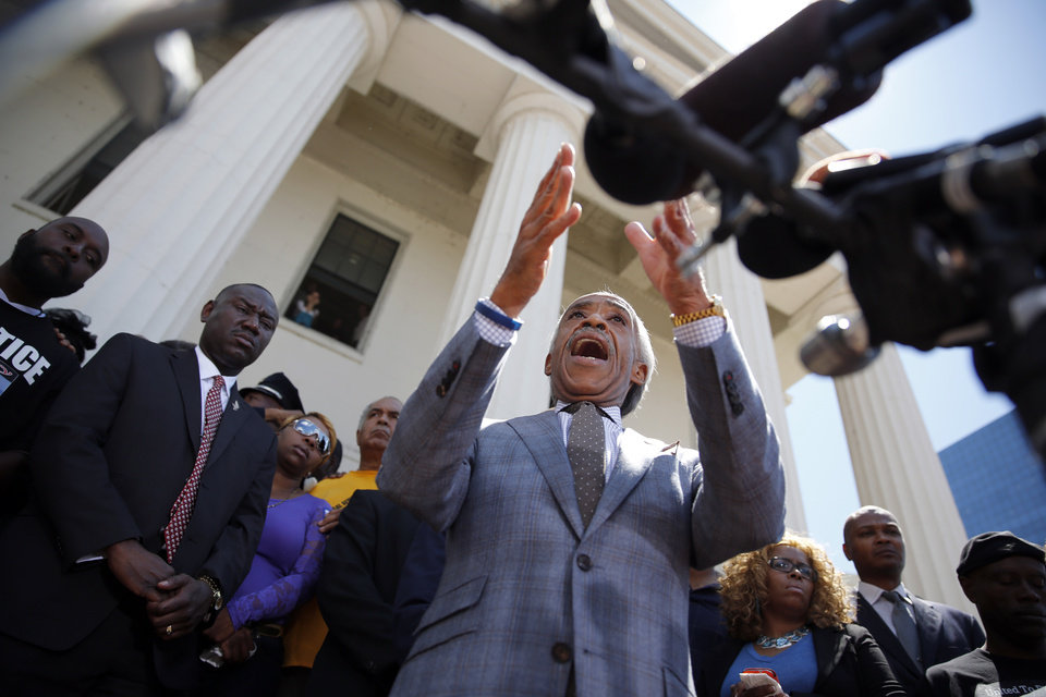 Photo - Civil rights activist Rev. Al Sharpton speaks during a news conference outside the Old Courthouse Tuesday, Aug. 12, 2014, in St. Louis. Michael Brown Jr., 18, who was unarmed, was shot to death Saturday by a Ferguson police officer while walking with a friend down the center of the street. (AP Photo/Jeff Roberson)