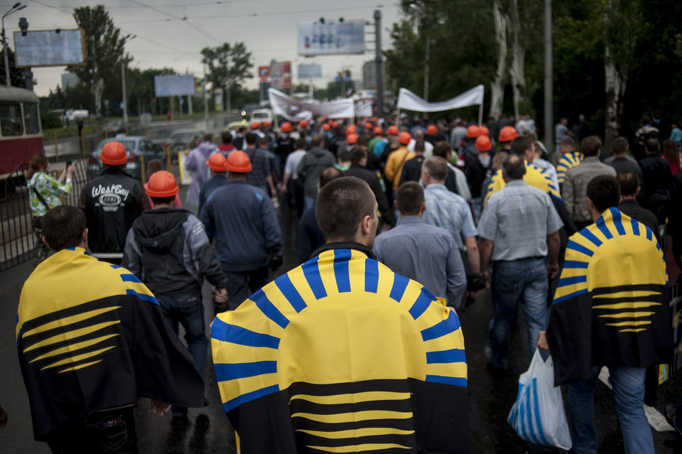 Photo - Miners, some of them with Donetsk regional flags on shoulders, march during a rally in support of peace in downtown Donetsk, eastern Ukraine, Wednesday, June 18, 2014.  Hundreds of miners went on a protest walk through the streets of central Donetsk on Wednesday, trying to express support for a peaceful resolution to the eastern Ukraine conflict, ongoing for almost four months. (AP Photo/Evgeniy Maloletka)