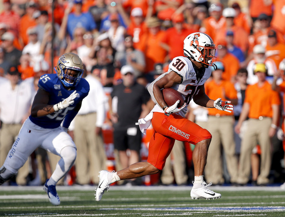 Photo - Oklahoma State's Chuba Hubbard (30) gets by past Tulsa's Yohance Burnett (35) as he rushes for a touchdown in the fourth quarter during a college football game between the Oklahoma State University Cowboys (OSU) and the University of Tulsa Golden Hurricane (TU) at H.A. Chapman Stadium in Tulsa, Okla., Saturday, Sept. 14, 2019. [Sarah Phipps/The Oklahoman]