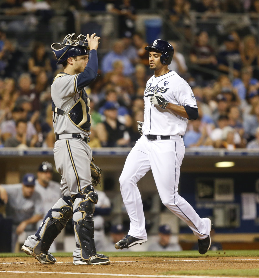 Photo - San Diego Padres starting pitcher Tyson Ross approaches home plate next to Milwaukee Brewers catcher Jonathan Lucroy to score during the third inning of a baseball game Tuesday, Aug. 26, 2014, in San Diego. (AP Photo/Lenny Ignelzi)