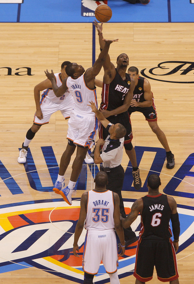 Oklahoma City's Serge Ibaka (9) and Miami's Chris Bosh (1) leap for the ball during the tipoff for Game 2 of the NBA Finals between the Oklahoma City Thunder and the Miami Heat at Chesapeake Energy Arena in Oklahoma City, Thursday, June 14, 2012. Photo by Bryan Terry, The Oklahoman