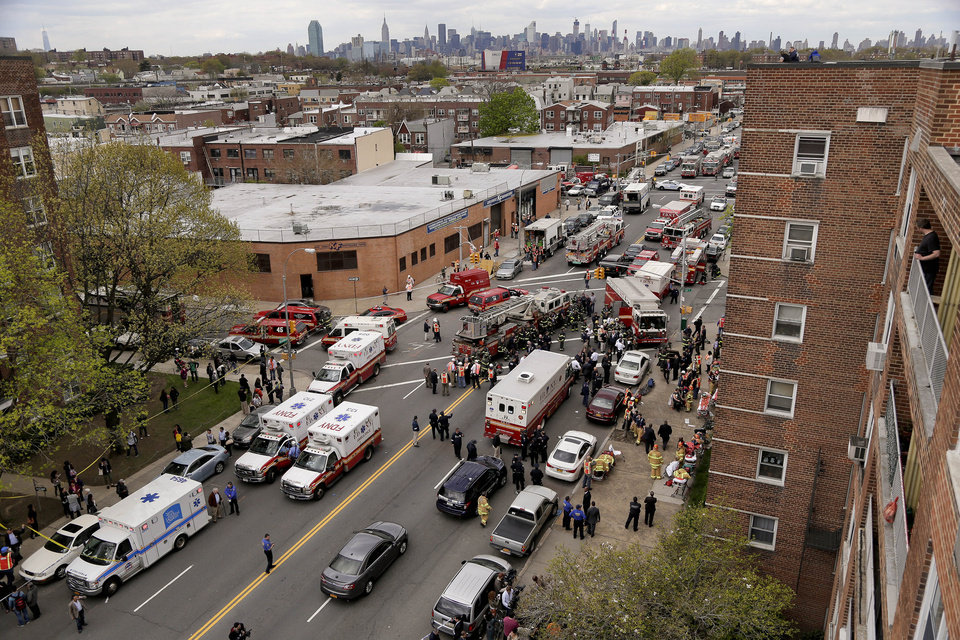 Photo - New York City emergency crews converge at 60th Street and Broadway to evacuate passengers from a subway train after it derailed in the Queens borough of New York, Friday, May 2, 2014.  The express F train was bound for Manhattan and Brooklyn when it derailed at 10:40 a.m. about 1,200 feet (365 meters) south of the 65th Street station, according to the Metropolitan Transportation Authority. Dozens of firefighters and paramedics with stretchers converged on Broadway and 60th Street, where passengers calmly left the tunnel through the sidewalk opening. A few were treated on stretchers. (AP Photo/Julie Jacobson)