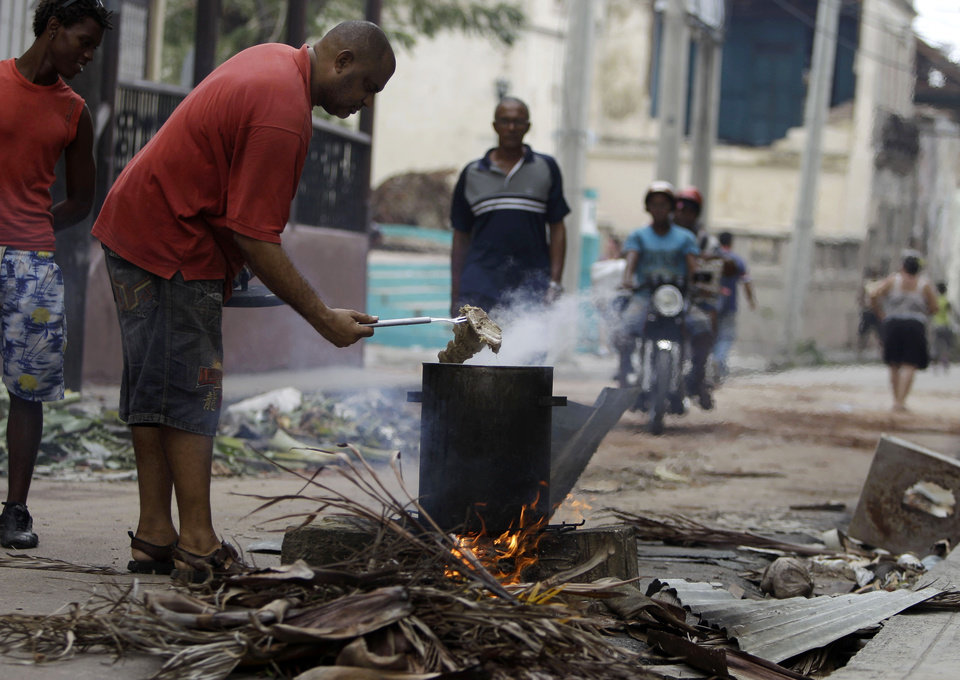 Photo -   A man uses burning wood to cook a traditional