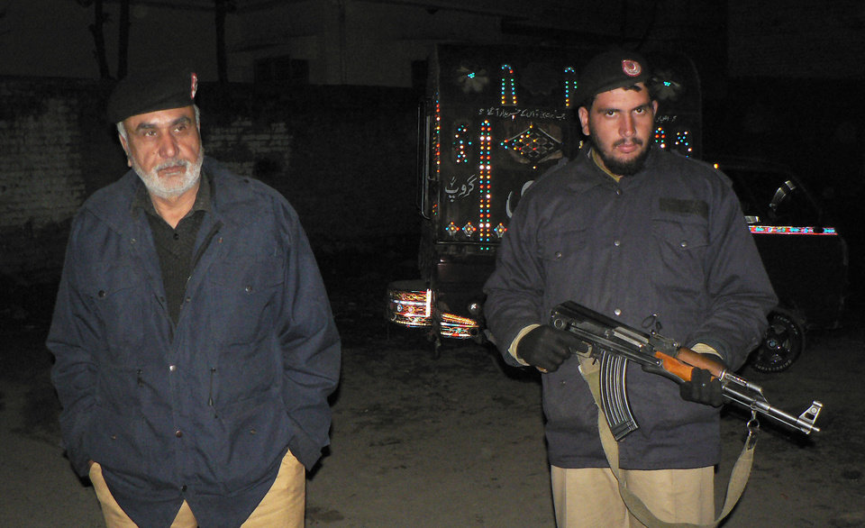 Photo -   Pakistani police officers stand guard in the vicinity of the compound of Osama bin Laden in Abbottatabd, Pakistan on Saturday, Feb 25, 2012. Local residents say Pakistan has started to demolish the compound in the northwest city of Abbottabad where Osama bin Laden lived for years and was killed by U.S. commandos. Two residents say the government brought in three mechanized backhoes Saturday, Feb. 25, 2012, and began destroying the tall outer walls of the compound after sunset. They set up floodlights to carry out the work. (AP Photo/Aqeel Ahmed)