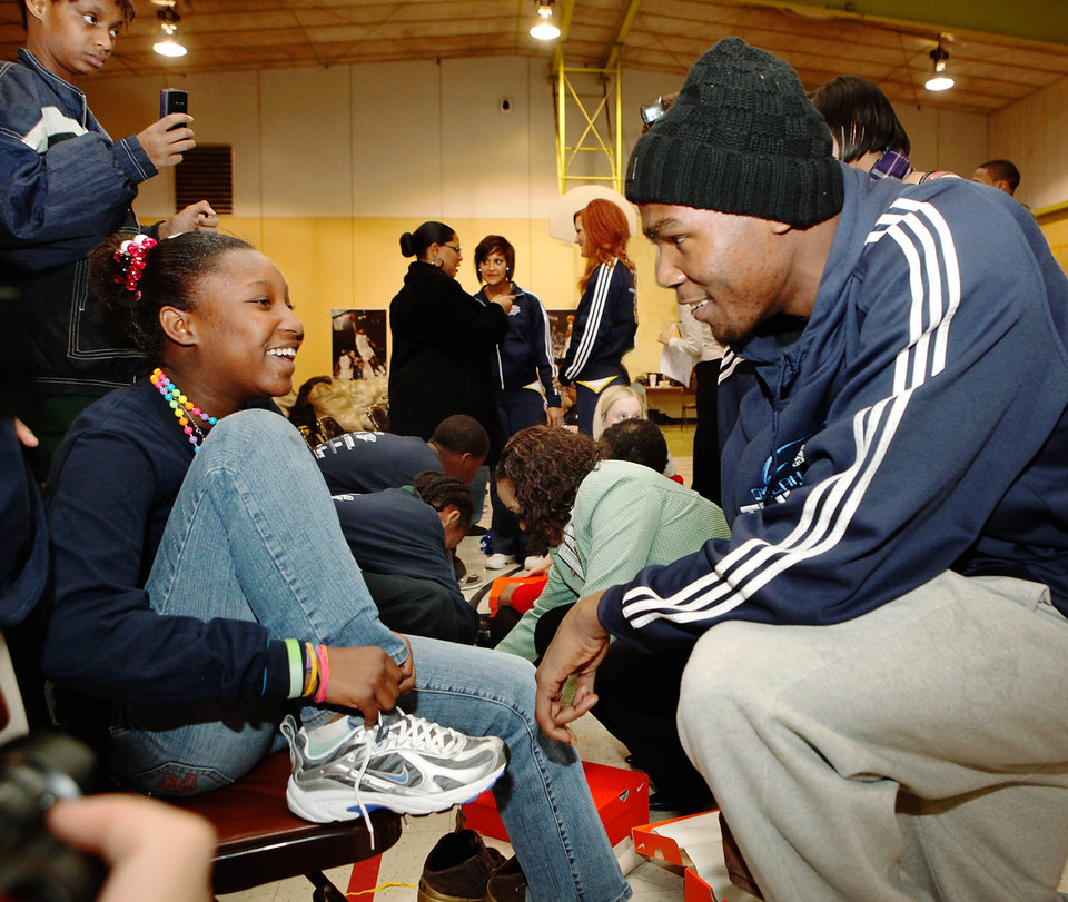 "Photo - Player Kevin Durant jokes with a student as she ties her new shoes. Players from the Oklahoma City Thunder NBA basketball team were joined by mascot, Rumble, and Thunder Girls in assisting children at Dunbar Elementary School  in trying on their new Nike athletic shoes donated by SandRidge employees Thursday, Dec. 17, 2009. Each player told the students their favorite holiday song.  Nick Collison: ""Frosty the Snowman"".  Russell Westbrook: ""Jingle Bells"".   Kevin Durant: ""Twelve Days of Christmas"".   Photo by Jim Beckel, The Oklahoman"