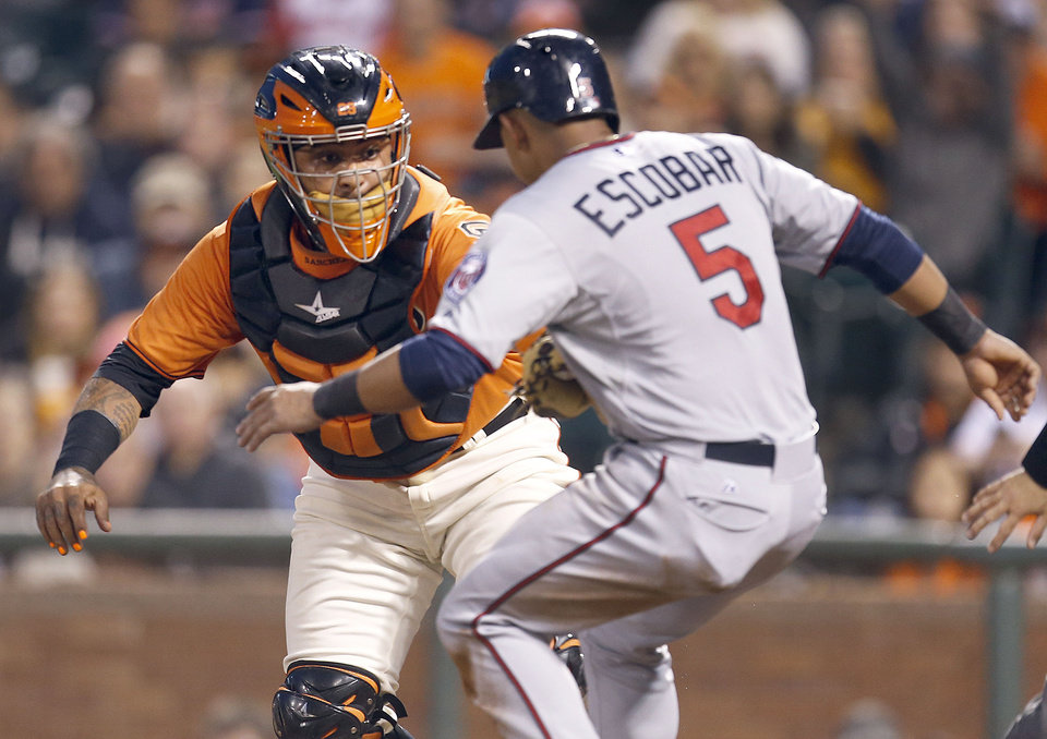 Photo - San Francisco Giants catcher Hector Sanchez (29) tags out Minnesota Twins' Eduardo Escobar (5) at home plate in the third inning of a baseball game Friday, May 23, 2014, in San Francisco. (AP Photo/Tony Avelar)