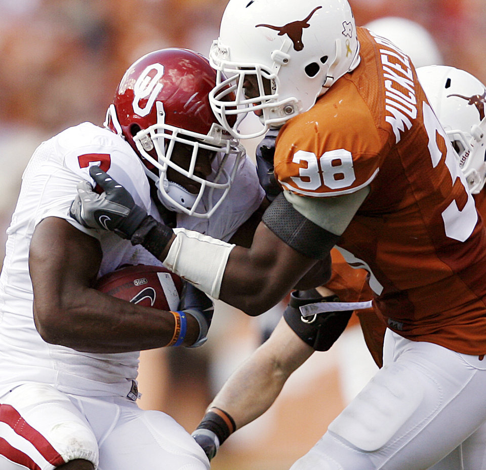 Photo - Texas' Roddrick Muckelroy (38) stops Oklahoma's DeMarco Murray (7) during the Red River Rivalry college football game between the University of Oklahoma Sooners (OU) and the University of Texas Longhorns (UT) at the Cotton Bowl in Dallas, Texas, Saturday, Oct. 17, 2009. Photo by Chris Landsberger, The Oklahoman