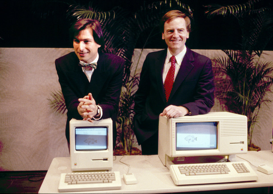 Photo - FILE -This January 1984, file photo, shows Steven P. Jobs, left and John Sculley presenting the new Macintosh Desktop Computer in January 1984 at a shareholder meeting in Cupertino, Calif. January 24, 2014, marks thirty years after the first Mac computer was introduced, sparking a revolution in computing and in publishing as people began creating fancy newsletters, brochures and other publications from their desktops. (AP Photo/FILE)